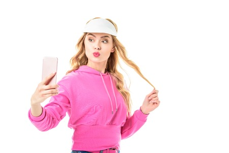 Attractive young woman dressed in pink taking selfie isolated on white Reklamní fotografie