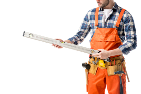 Close-up view of spirit level in hands of workman in orange overall isolated on white Stockfoto