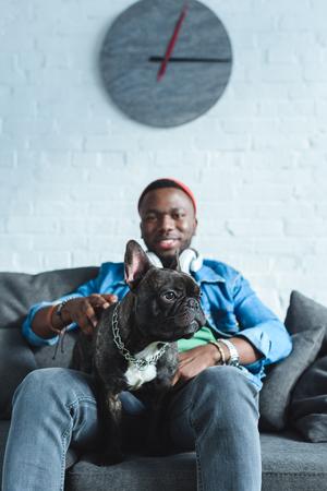 Handsome african american man in headphones cuddling French bulldog Stock fotó