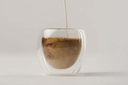 Pouring milk in cup with coffee isolated on white background Stok Fotoğraf