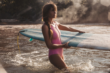 young woman carrying surfing board in hands while walking into ocean Stok Fotoğraf