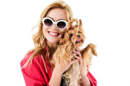 Attractive young woman dressed in pink holding cute Yorkie isolated on white