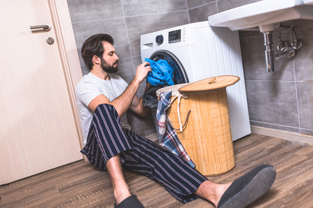 handsome loner putting laundry in washing machine in bathroom Stock Photo