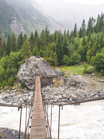 wooden bridge above rapid river in beautiful mountains, Georgia