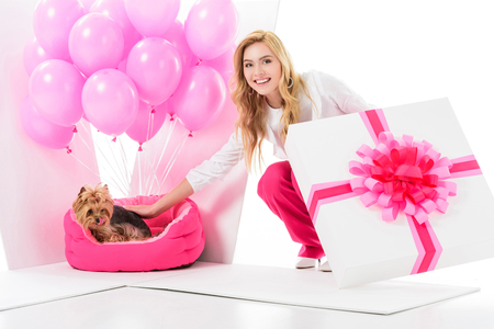 Blonde woman in pink clothes surprised by Yorkshire terrier in gift box isolated on white