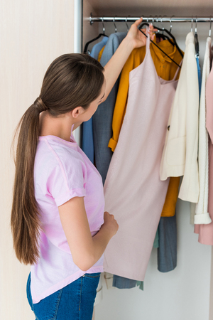 attractive young woman choosing clothes from rack