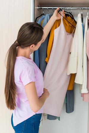 attraente giovane donna che sceglie i vestiti dallo scaffale