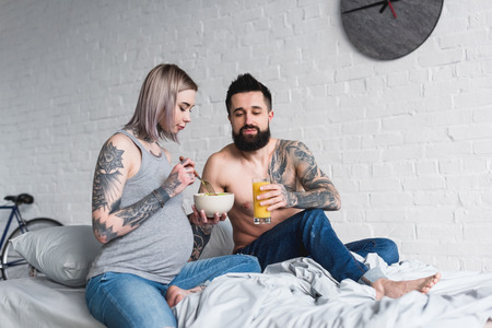 pregnant tattooed girlfriend eating salad on bed
