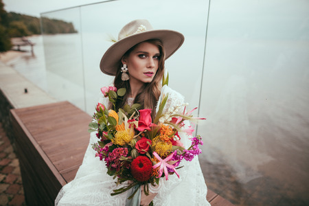 attractive bride in bohemian wedding dress and hat with bouquet Stock fotó - 111580545