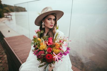 jolie mariée en robe de mariée bohème et chapeau avec bouquet Banque d'images