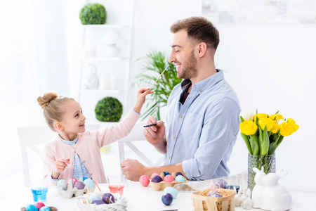 Young man and child girl painting Easter eggs