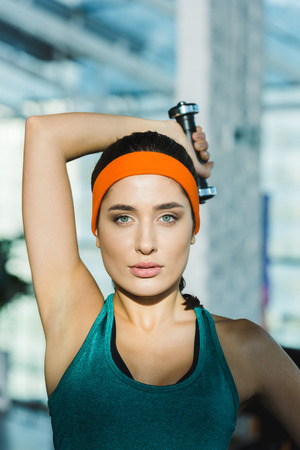 sporty woman training with dumbbell and looking at camera