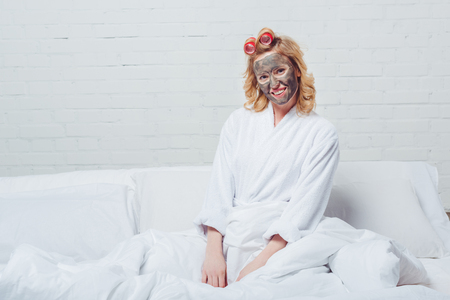beautiful woman in bath robe with facial mask sitting in bed Archivio Fotografico - 111580614