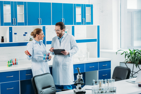 scientific researchers in white coats and eyeglasses with flasks and notepad in laboratory