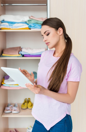 attractive young woman using tablet at home near cabinet with clothes Stock Photo - 111580626