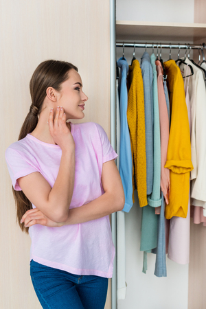 thoughtful young woman looking at clothes hanging in cabinet at home
