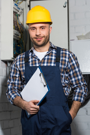 Electrician holding clipboard and smiling by electrical box
