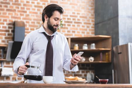 handsome loner businessman holding pot with coffee and smartphone at kitchen Stock Photo