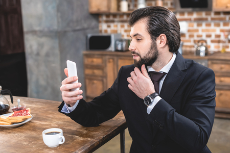 side view of handsome loner businessman taking selfie with smartphone at kitchen