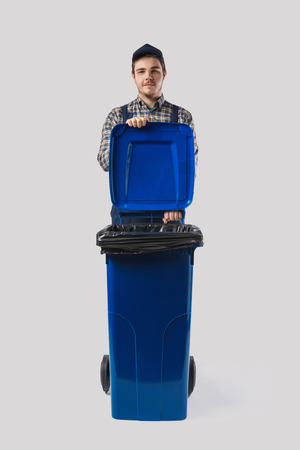 portrait of young cleaner in uniform with trash bin isolated on grey