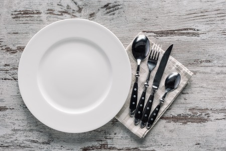 white plate and cutlery on napkin on wooden table