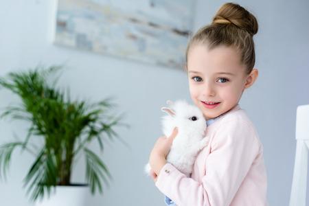 Child girl cuddling white bunny