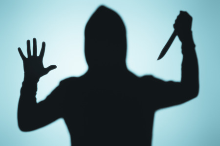scary shadow of person in hood holding knife on blue Reklamní fotografie - 111580944