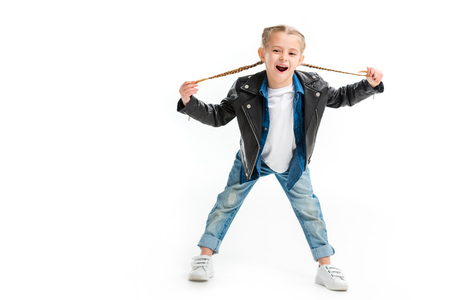 Excited child in black leather jacket holding her pigtails isolated on white