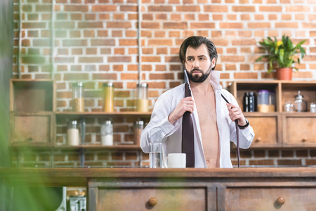 handsome loner businessman with unbuttoned shirt looking away at kitchen Stock Photo