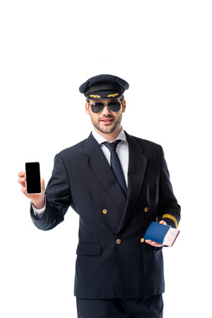 portrait of pilot in uniform with passport and ticket in hand showing smartphone with blank screen isolated on white 스톡 콘텐츠