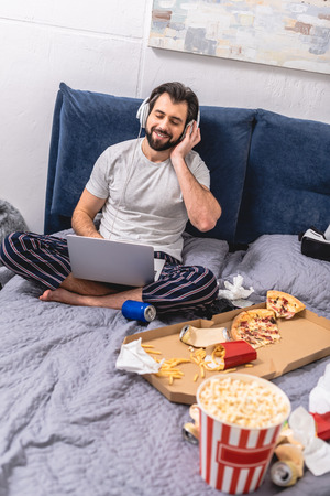 handsome loner listening music with laptop in bedroom Stock Photo