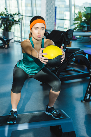 sporty woman training with medicine ball at gym