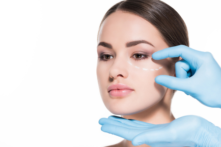close-up shot of doctor touching face of woman with dotted line for plastic surgery isolated on white Stock Photo