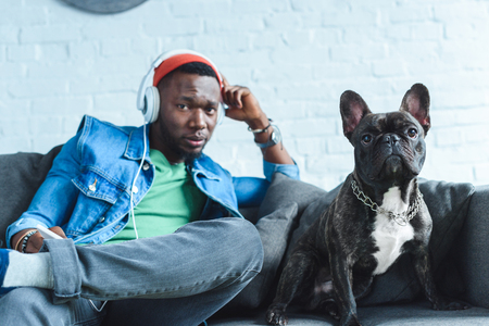 Young man in headphones listening to music and sitting by French bulldog Banco de Imagens