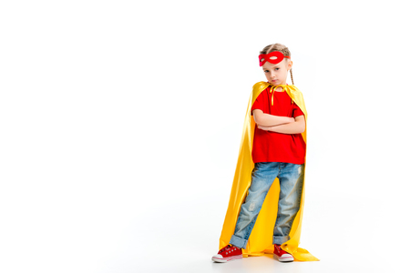 Grumpy little supergirl wearing yellow cape with red mask for eyes on forehead isolated on white