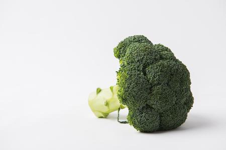 green raw brocolli laying on white background