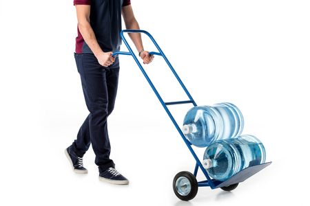 partial view of delivery man in uniform pushing hand truck with large bottles of water isolated on white