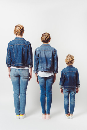 back view of family in similar denim clothing standing in row isolated on grey
