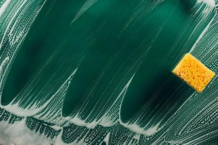 widok z góry gąbki myjącej i pianki na zabrudzonej powierzchni
