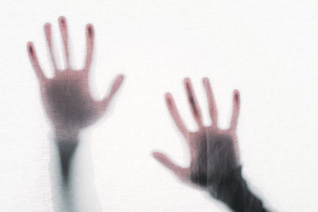 blurry silhouette of human hands touching frosted glass