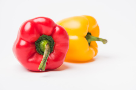 red and yellow raw bell peppers laying on white background