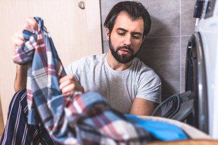 handsome loner taking clothes for washing near washing machine in bathroom