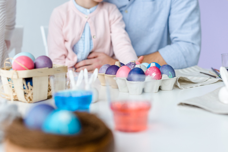 Painted Easter eggs on table in front of child and parents Stock Photo