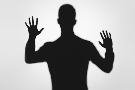 mysterious blurry shadow of person raising hands on grey Stockfoto
