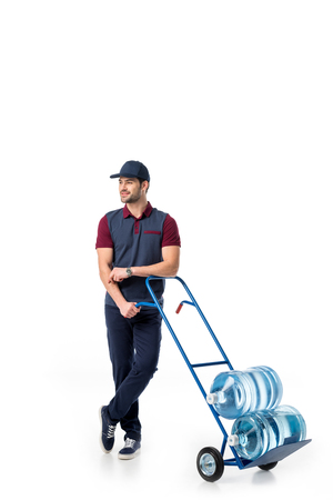 smiling delivery man with large bottles of water on hand truck isolated on white Stock Photo