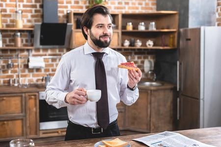 handsome loner businessman having breakfast at kitchen Stock Photo