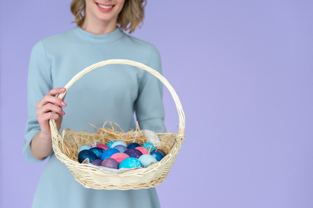 Close-up view of woman with painted eggs in Easter basket colored eggs isolated on violet