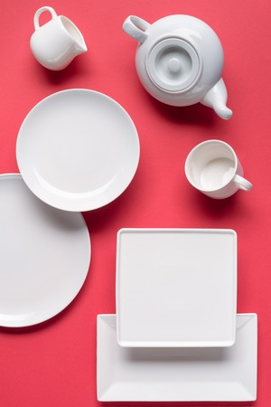 White crockery plates and tea-set on red background