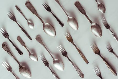 Cucharas y tenedores vintage en mesa blanca Foto de archivo