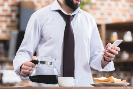 cropped image of loner businessman holding pot with coffee and smartphone at kitchen Stock Photo